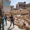 叙利亚阿勒颇东部,放学回家的儿童走过一片废墟。