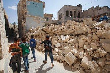 طلاب مدارس في شرقي حلب في الجمهورية العربية السورية يعودون من أول يوم دراسي ويسيرون بين منازل مدمرة على جنبات الطريق. (21 أيلول/سبتمبر 2016)