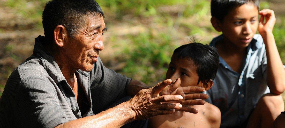 Un hombre mayor cuenta relatos a los niños según la tradición oral mapoyo.