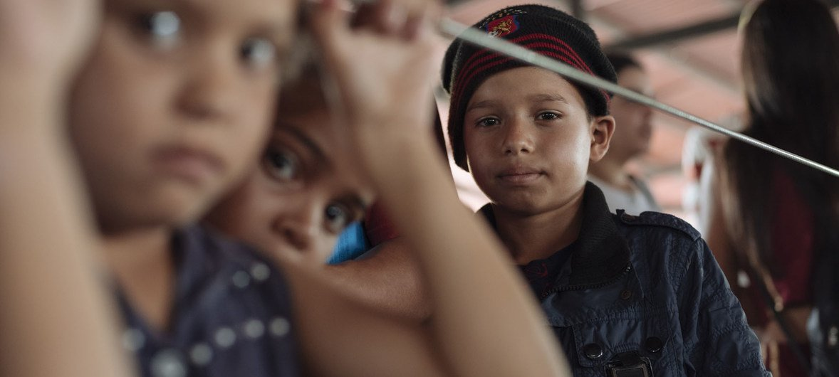 Ten-year old Jimmy (right), one of millions of Venezuelan fleeing the country, waits in the migration center queue to get his official papers to enter Ecuador, where his sister is waiting for him. (2019)