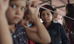 वेनेजुएला से घर छोड़कर भागने वाले लाखों लोगों में से एक दस-वर्षीय जिमी (दाएं) है. इक्वाडोर में प्रवेश के आधिकारिक कागज़ात प्राप्त करने के लिए माइग्रेशन सेंटर की कतार में प्रतीक्षा कर रहा है. (2019)