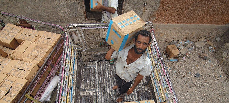 Trabajadores organizan cajas con ayuda alimentaria del PMA en Lahj, Yemen.