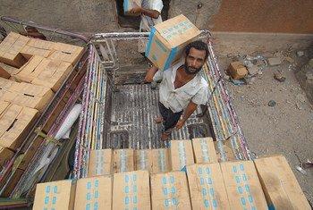 Des travailleurs emplie de l'aide alimentaire dans un entrepôt à Lahj, au Yémen. (1er juillet 2019)