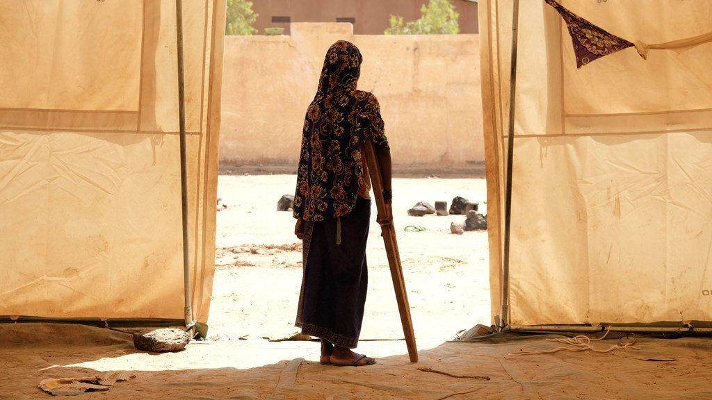 Une jeune fille utilise une béquille pour marcher dans un camp de déplacés, dans la région de Mopti, au Mali (juin 2019).