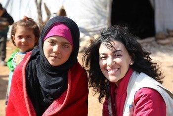 مروة عوض، المتحدثة باسم برنامج الأغذية العالمي في سوريا مع إحدى المستفيدات من مساعدات البرنامج.