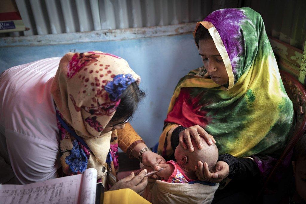 Une volontaire d'un centre de santé dans l'un des vastes camps de réfugiés de Cox's Bazaar, au Bangladesh, inocule le bébé d'une mère de 18 ans.