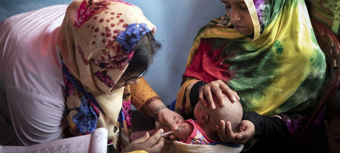 Uma voluntária no Centro de Saúde Primário no acampamento de refugiados de Cox's Bazaar imuniza bebê de uma mãe de 18 anos, Bangladesh 2019.
