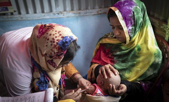 A volunteer at the Primary Health Centre in on of Cox's Bazaar's vast refugee camps inoculates the baby of an 18-year-old mother, Bangladesh 2019.
