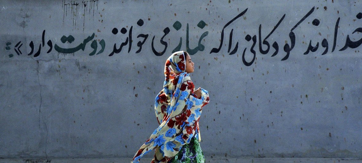 """A girl wearing her hijab in Iran runs past a mural stating, in Persian, """"God loves children who say their 'namaz' [prayers]."""" (File)"""
