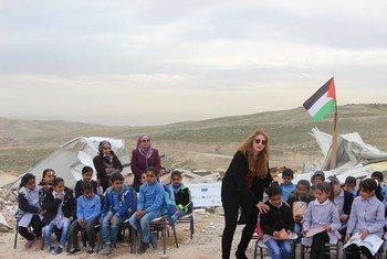 """الدكتورة سحر القواسمة، المديرة العامة لمؤسسة """"أدوار"""" مع طلاب فلسطينيين."""