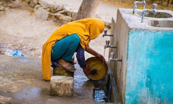 Женщина в Пакистане наполняет канистру питьевой водой из колонки