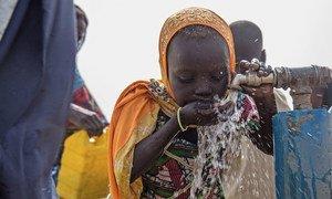 A young girl drinks water in the Bakassi IDP camp, in Maiduguri, Nigeria.