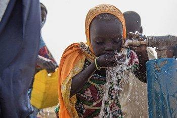 Menina bebe água em campo para pessoas deslocadas pela violência