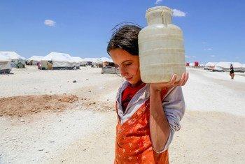 فتاة تحمل المياه في مخيم مؤقت في عين عيسى بسوريا.
