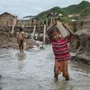 A young boy carries water in Cox's Bazar, Bangladesh.