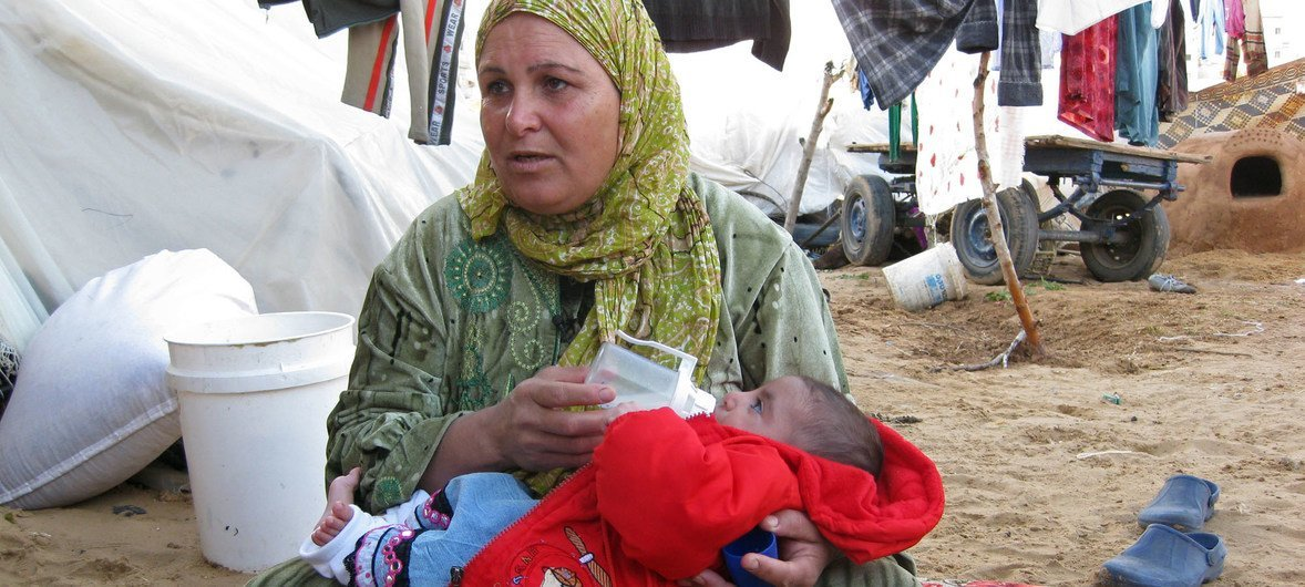 A Displaced woman feeds a child in Gaza. (File)