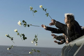 """Visitors throw white flowers into Rio de la Plata in Buenos Aires out of respect and remembrance for the tens of thousands of people who disappeared during Argentina's so-called """"Dirty War""""."""