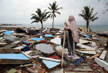 Una mujer observa su pueblo en Indonesia, destruido por un tsunami.