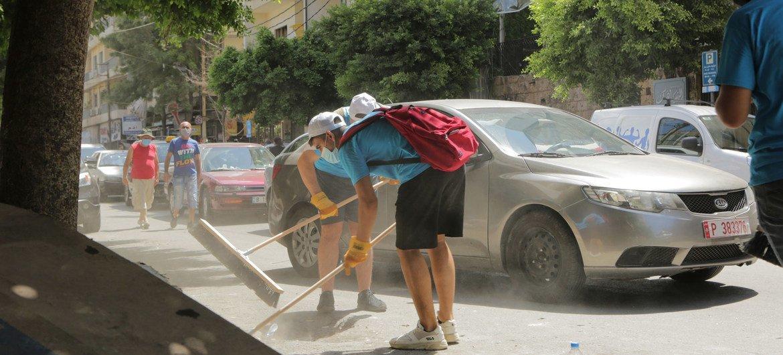 متطوعون ضمن شبكة شبابية أنشأتها اليونيسف ينظفون الشوارع عقب انفجار المرفأ في بيروت.