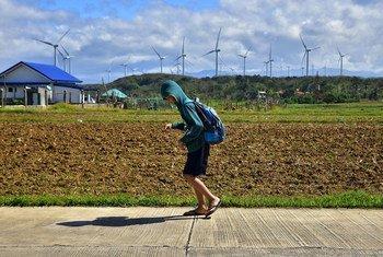 菲律宾的一名学生正经过一座150兆瓦的风力发电场。