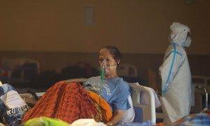 在印度新德里一个又宴会厅临时改建的急诊病房,一名新冠患者正在接受治疗。
