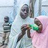 विश्व खाद्य कार्यक्रम से प्राप्त राहत सामग्री की मदद से एक मां अपने बच्चों को भोजन दे रही है.