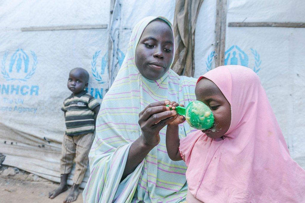 Une mère prépare de la nourriture pour ses enfants avec des céréales qu'elle a reçues d'un site de distribution du Programme alimentaire mondial (PAM) à Maiduguri, au Nigeria.