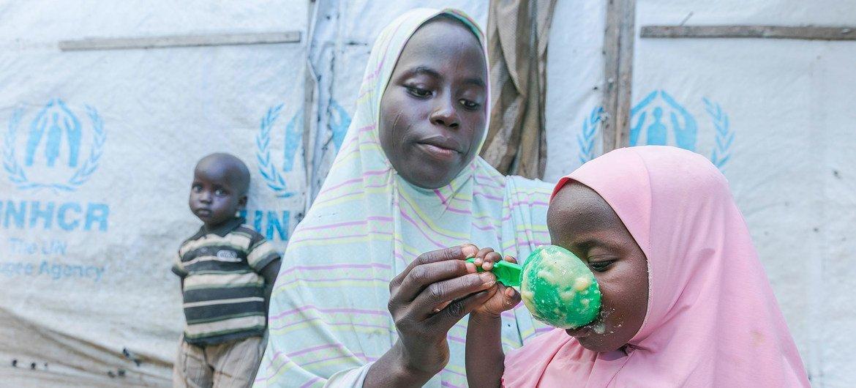 Una madre alimentando a sus hijos con cereales que ha recibido en un punto de distribución del Programa Mundial de Alimentos en Maiduguri, Nigeria