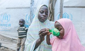 A mother prepares food for her children with cereal she received from a World Food Programme (WFP) distribution site in Maiduguri, Nigeria.