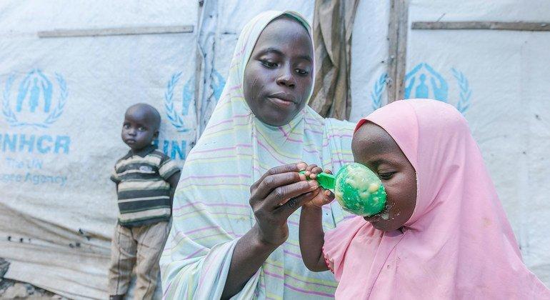 أم في نيجيريا تعد الطعام لأبنائها وتقدم لهم الحبوب التي يوفرها برنامج الأغذية العالمي.