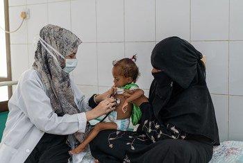 यमन में एक माँ, अपनी 18 महीने की बच्ची का कुपोषण के लिये इलाज कराते हुए.