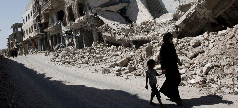 सीरिया के इदलिब में, मरात अल-नुमान शहर में एक युवा लड़की और एक महिला, तबाह इमारतों के पास से जाते हुए.