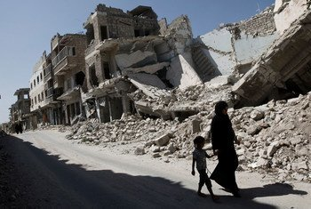 Mtoto wa kike na mwanamke wakitembea kupita majengo yaliyoharibiwa katika jiji la Maarat al-Numaan huko Idlib, Syria.