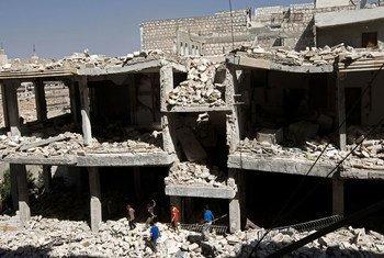 (من الأرشيف) أطفال يتجولون وسط أنقاض المباني المدمرة في إدلب، سوريا.