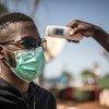 माली में कोविड-19 के सम्भावित संक्रमण के बारे में एहतियात के तौर पर एक व्यक्ति के तापमान की जाँच होते हुए.