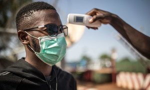 A man's temperature is taken in Mali to check against a possible COVID-19 infection.