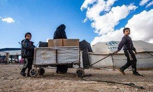 أسرة تحصل على الملابس استعدادا لفصل الشتاء من اليونيسف في مخيم الهول شمال شرق سوريا.