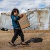 सीरिया के उत्तरी हिस्से में, अल होल शिविर में, यूनीसेफ़ द्वारा वितरित, सर्दियों के कपड़ों का गट्ठर ले जाते हुए एक बच्ची.