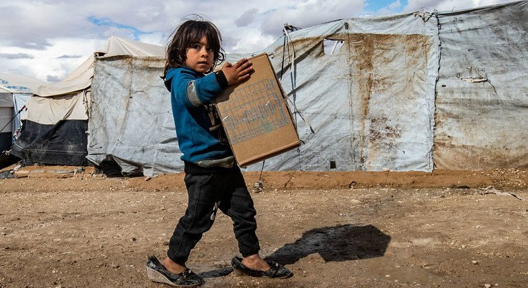 A child carries winter clothing kits, distributed by UNICEF, in Al-Hol camp in northeastern Syria.