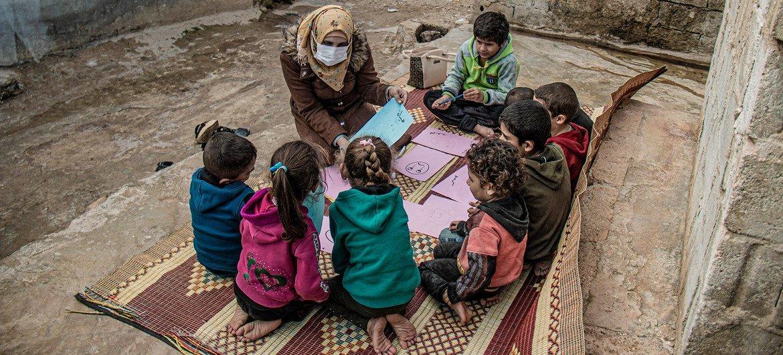 叙利亚西北部的流离失所者营地内,一位医务人员正与几名儿童交谈。