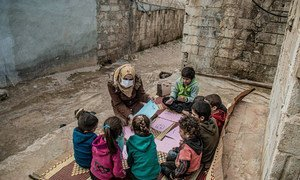 A health worker talks to displaced children about their hopes and worries in Atma camp, Syria.