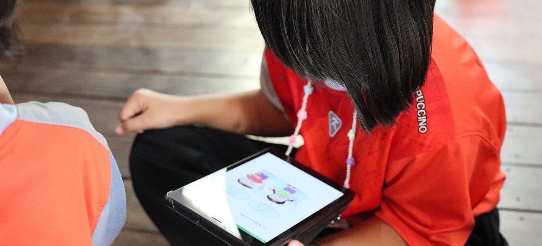 Estudante lê em um tablet em uma escola na Tailândia