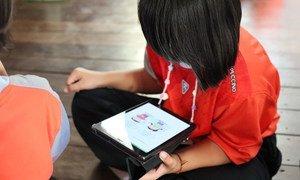 Une apprenante lit sur une tablette à l'école Ban Mae Sa Nga de Mae Hong Son, en Thaïlande.