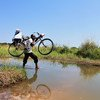 A health worker crosses a stream with his bike on his way to vaccinate children in Tanganyika Province in the Democratic Republic of the Congo.