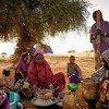 Displaced women prepare food at an informal camp in Bagoundié, Mali.