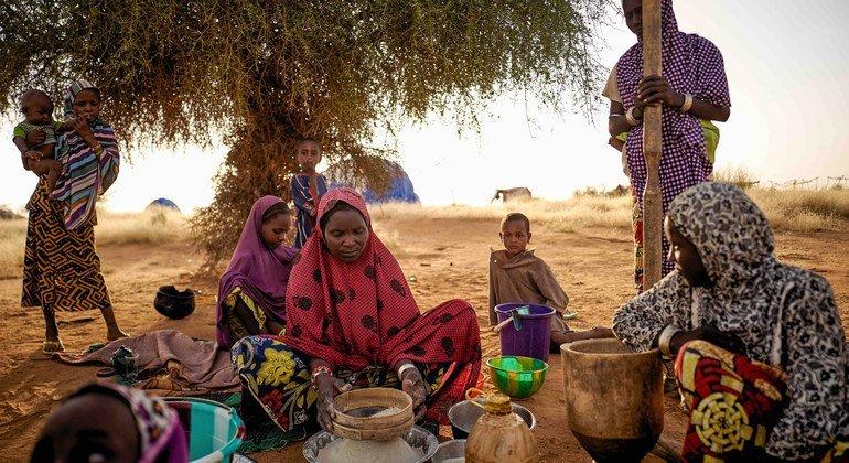 Sahel : des femmes déplacées préparent de la nourriture dans un camp informel à Bagoundié, au Mali.