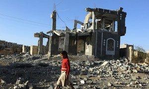 A girl walks through the rubble of war in Sana'a, Yemen.