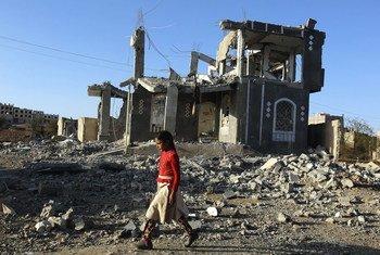 فتاة تسير أمام أنقاض مبانٍ مدمرة بسبب الحرب في صنعاء باليمن.