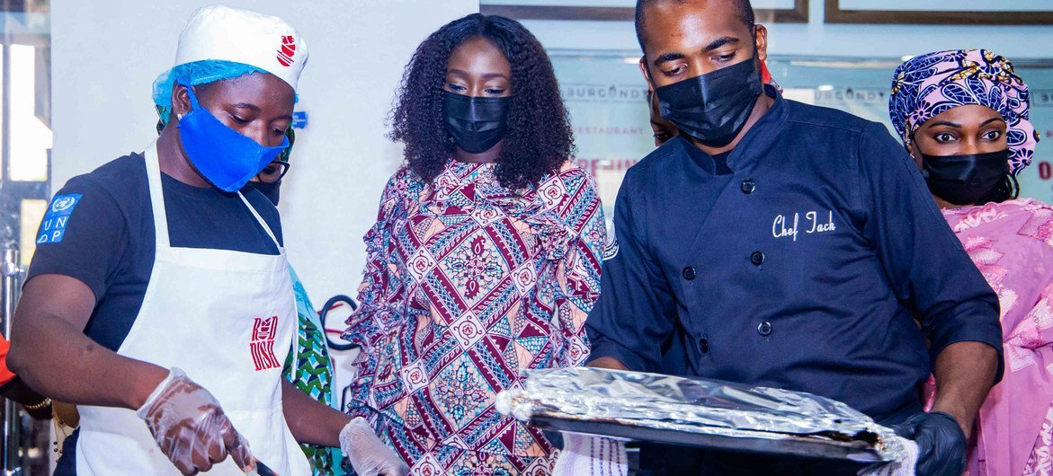 Blessing Ojukwu (left) leant how to cook pastry and other foods at a UN-supported initiative.