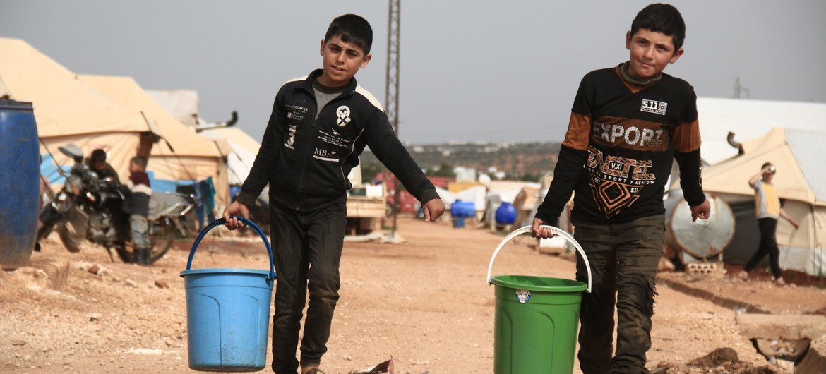 Two children collect drinking water at a camp for the displaced in Idlib, Syria.